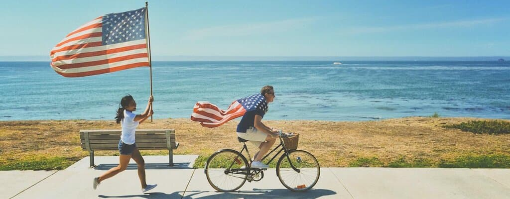 US Green Card - A man riding a bike and a woman running behind carrying a US flag
